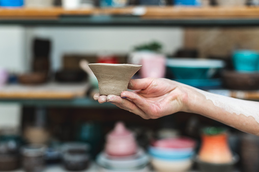 Master class concept. Cropped close up photo of workmanship lady in her workwear she stand against blurred wooden shelf background indoor workspace hold small ceramics clay tea cup on hand
