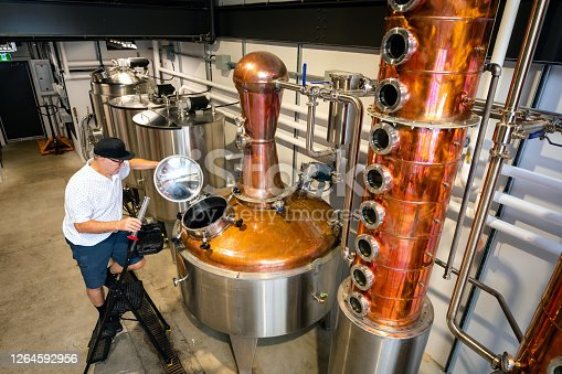 Senior entrepreneur working at a distillery. Craft brewing spirits at a small business. Skilled senior worker.