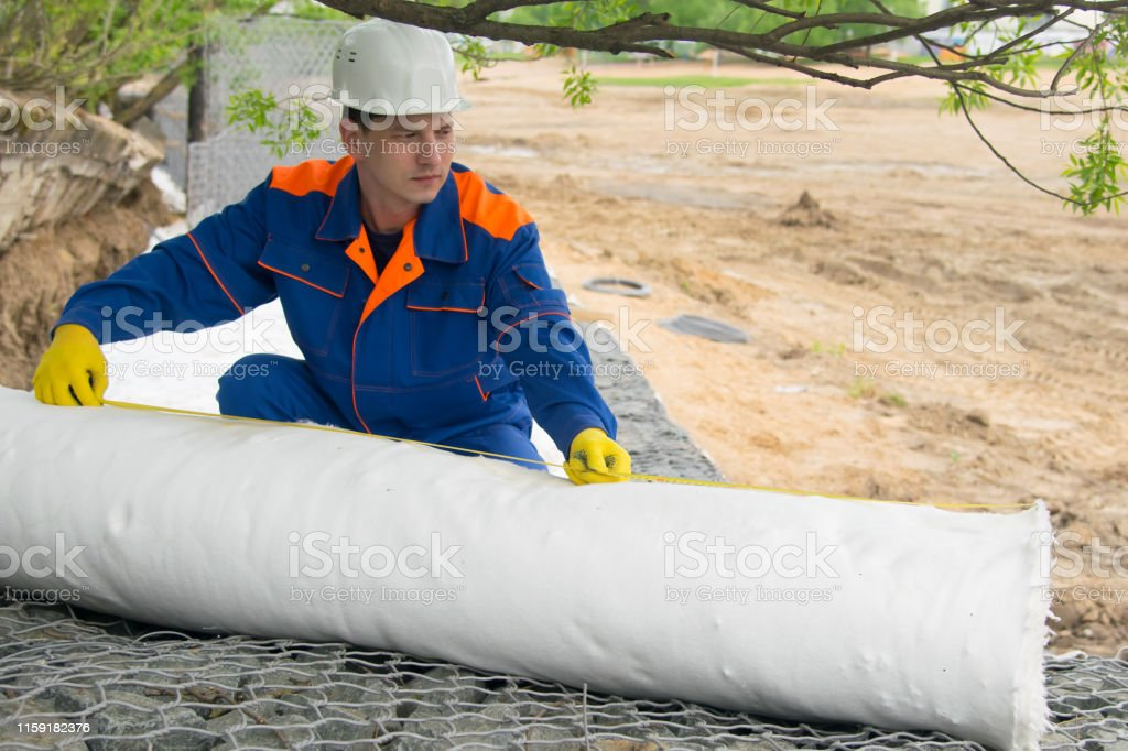 master in blue uniform and protective helmet, rolls out a roll of...