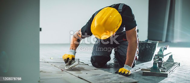 A bearded man in overalls working on a tile floor, filling the joints with grout.