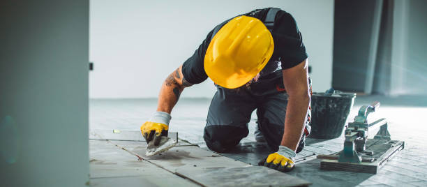 Master installer laying tile A bearded man in overalls working on a tile floor, filling the joints with grout. business stock pictures, royalty-free photos & images