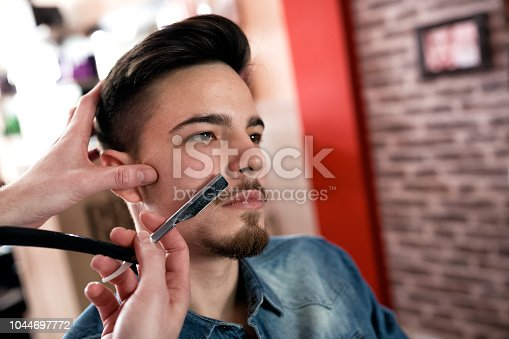928445950 istock photo Master makes  moustache correction with a blade 1044697772