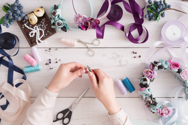 Master making handmade jewelry, top view Master making handmade jewelry, top view. Needlewoman workplace with plastic beads, flowers and tools for creating accessories craft product stock pictures, royalty-free photos & images