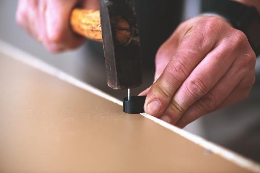 Master man hammers a nail into furniture