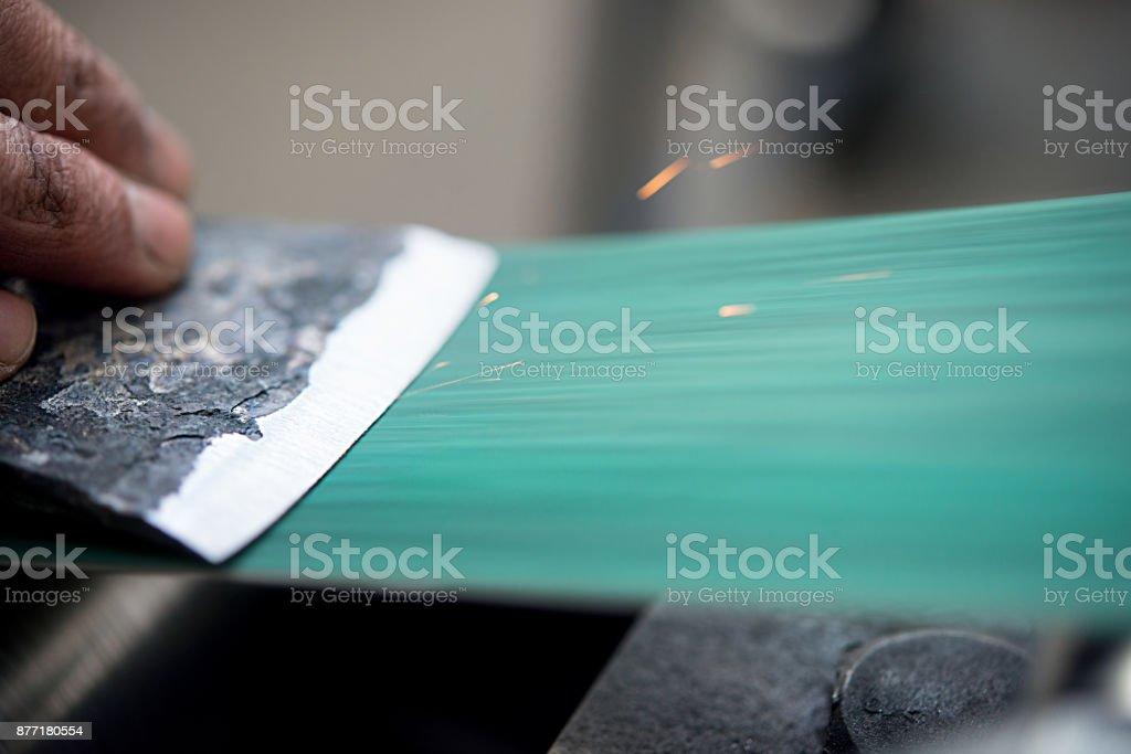 Master Man schärft die Axt auf der Schleifmaschine – Foto