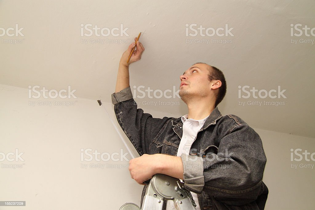 Master measures location for drilling on the ceiling royalty-free stock photo