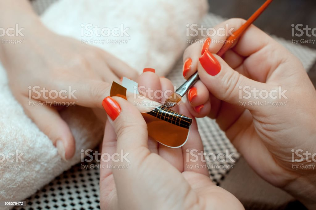 Master of manicure makes nail extensions gel stock photo