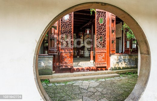 Suzhou, China - Nov 5, 2016: Master of Nets Garden (Wang Shi Yuan) – Moon gate doorway leading into a small residential courtyard designed in the classical Chinese architecture style, with some bamboo bush in front.