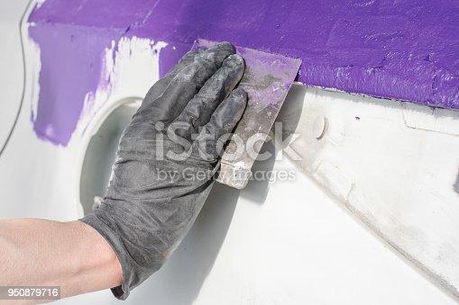 istock Master performs car body repair 950879716