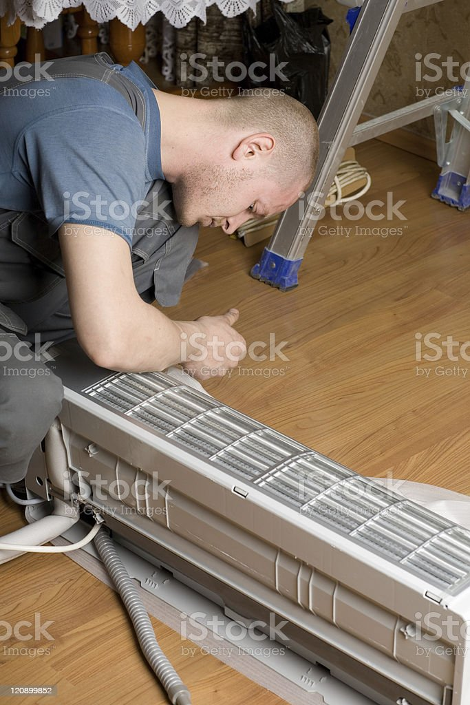 master prepares a new air conditioner to be installed royalty-free stock photo