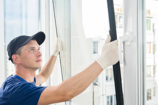 master legt ein neues doppelt verglastes fenster in ein kunststofffenster - fensterbauer stock-fotos und bilder