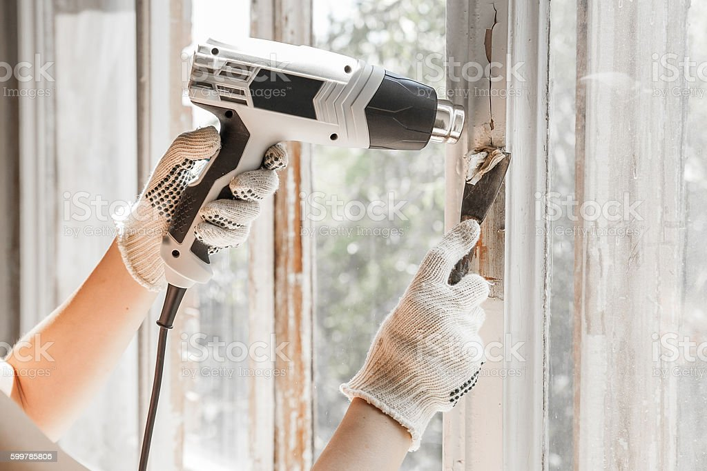 Master removes old paint from window heat gun and scraper. stock photo