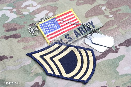 istock US ARMY Master Sergeant rank patch, flag patch, with dog tag on camouflage uniform 1190926101