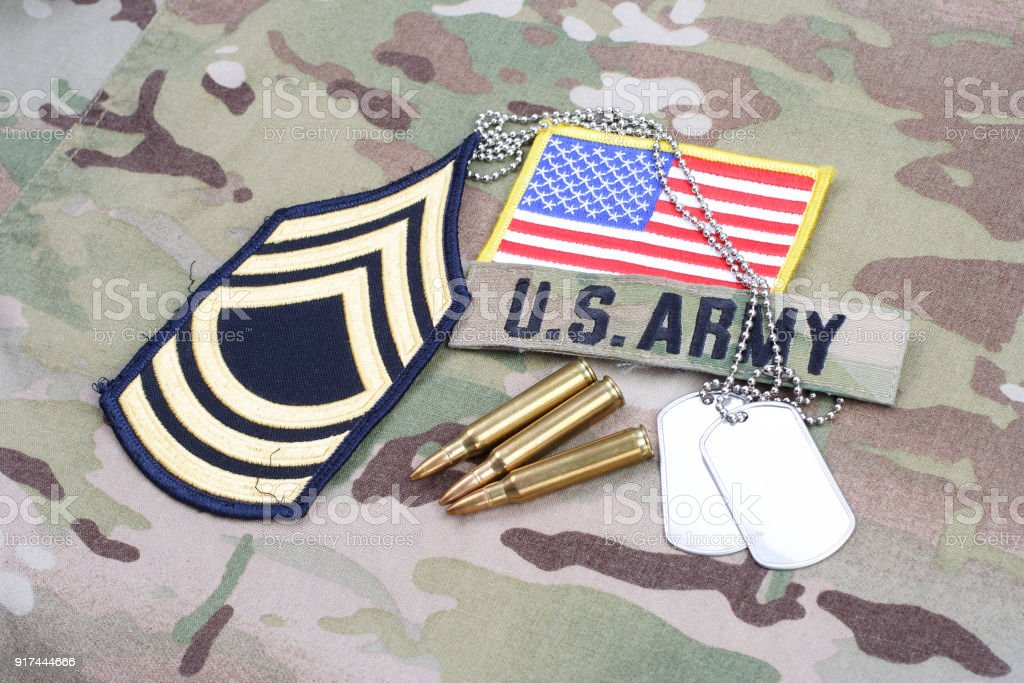 US ARMY Master Sergeant rank patch, flag patch, with dog tag with 5.56 mm rounds on camouflage uniform stock photo