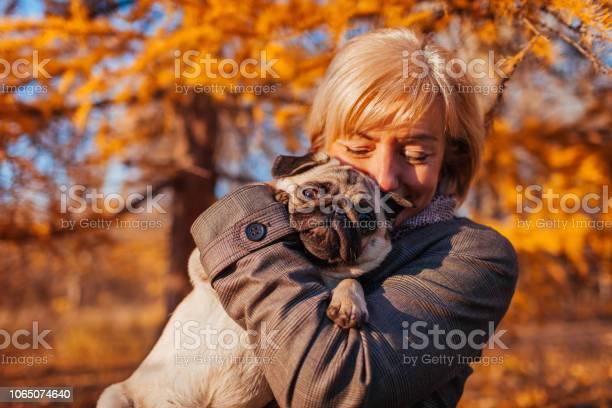 Master walking pug dog in autumn park happy woman hugging pet human picture id1065074640?b=1&k=6&m=1065074640&s=612x612&h=xcvcscnawwhxbz2o n7fkap1cpcaop btf unzmhbum=
