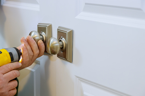 Master with screwdriver installs access the room door new dummy lock in house.