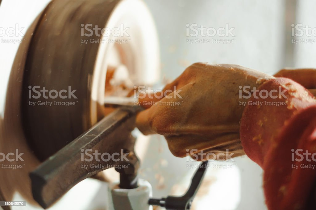 master working on a lathe on wood acceleration stock photo