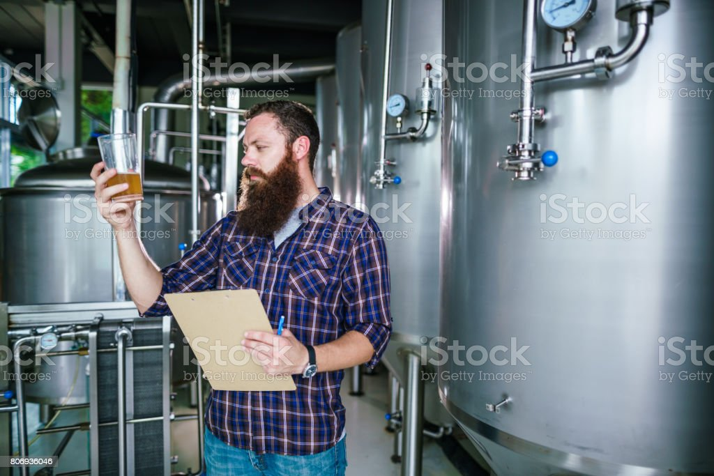 Master works in the brewery: beer testing, making remarks, quality control stock photo