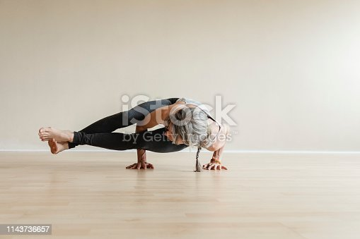 Adult woman wearing gray sportswear working out in indoor. Fit yogi woman doing Eight-angle pose, Astavakrasana.