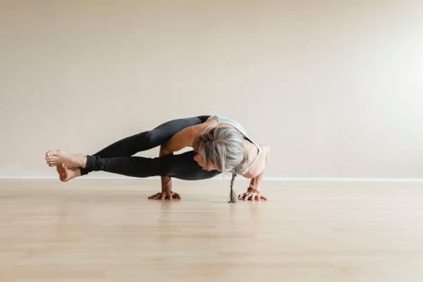 master yoga woman doing eight-angle pose, astavakrasana. - aktywny tryb życia zdjęcia i obrazy z banku zdjęć