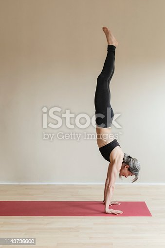 Adult woman wearing gray sportswear working out in indoor. Fit yogi woman doing Handstand, Adho Mukha Vrksasana.