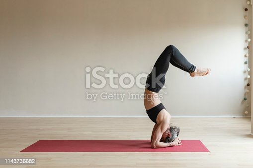 Adult woman wearing gray sportswear working out in indoor. Fit yogi woman doing Headstand, Sirsasana.
