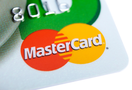 Istanbul, Turkey - February 12, 2012: MasterCard logo on credit card MasterCard Worldwide is an American multinational corporation. Its principal business is to process payments between the banks of merchants and the card issuing banks or credit unions of the purchasers who use the