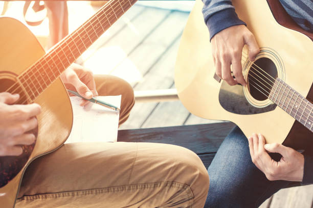 Masterclass learning to play the guitar outdoors. Musical education. stock photo