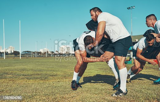 Shot of rugby players training with tackle bags on the field