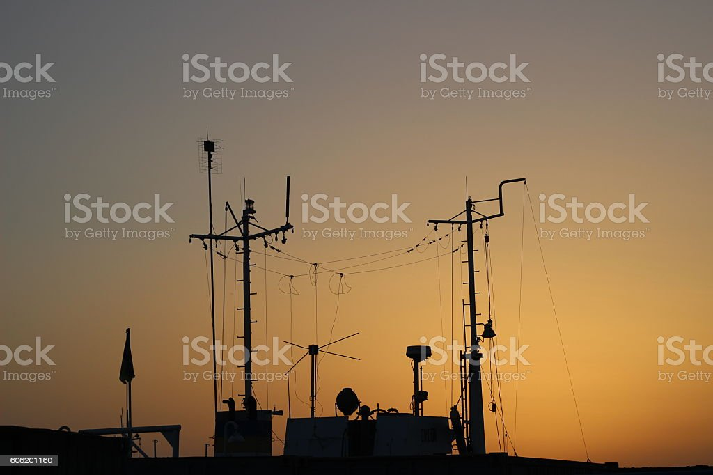 Masts silhouettes on sea and sunset sky background stock photo