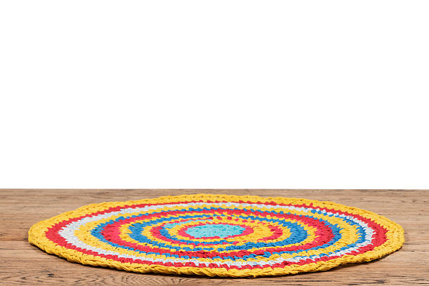 Mat of small cords handmade Colorful handmade rug made from old rags, lying on a wooden table isolated on white background peruvian culture stock pictures, royalty-free photos & images