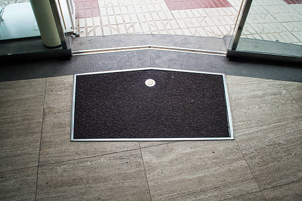 Mat on the gray stone floor near glass sliding door Black with metal frame mat on the gray stone floor near metal glass sliding door entrance sign stock pictures, royalty-free photos & images