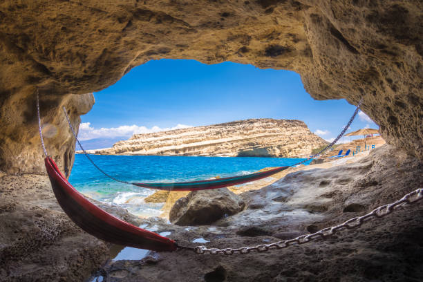 Matala beach with caves on the rocks that were used as a roman cemetery and at the decade of 70's were living hippies from all over the world, Crete, Greece stock photo