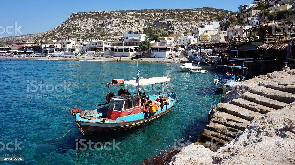 Matala village Matala village with fishing boat in Crete. Greece 2015 Stock Photo