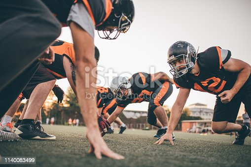 Group of men, American football players on rough training outdoors.