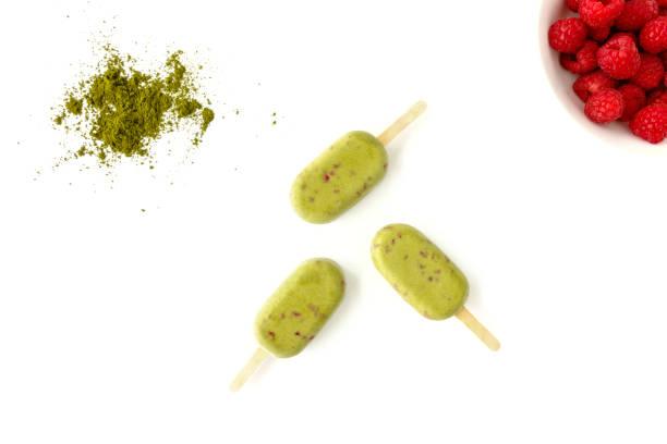 matcha und himbeer eis am stiel auf weißem hintergrund - grüner tee koffein stock-fotos und bilder