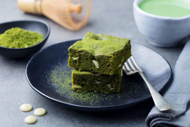 matcha-grüntee-kuchen, bars, brownie mit weißer schokolade auf einem teller. grau hinterlegt. - grüntee kuchen stock-fotos und bilder