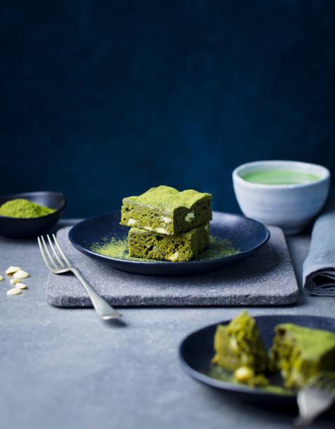 matcha grüner tee-kuchen, bars, brownie mit weißer schokolade auf einem teller. grauer steinhintergrund. platz kopieren. - grüntee kuchen stock-fotos und bilder