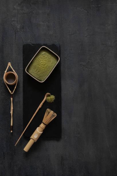 Kit de cerimônia de chá verde matcha - matcha em pó, colher de pau, coador e bater em um fundo cinza escuro - foto de acervo