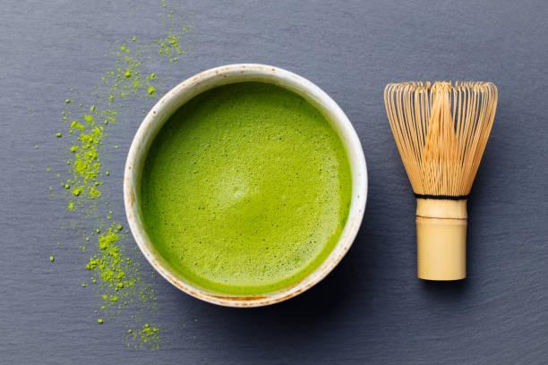 抹茶は、茶筅をボウルにプロセスを調理します。黒いスレートの背景。平面図です。 - 抹茶 ストックフォトと画像