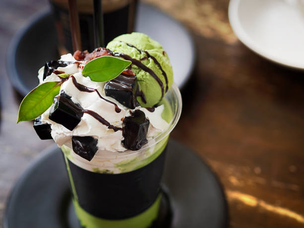 Matcha green tea frappe decorated with whipped cream, green tea ice cream, grass jelly and mint served on wooden table in a cafe, coffee shop for dessert and drinks stock photo