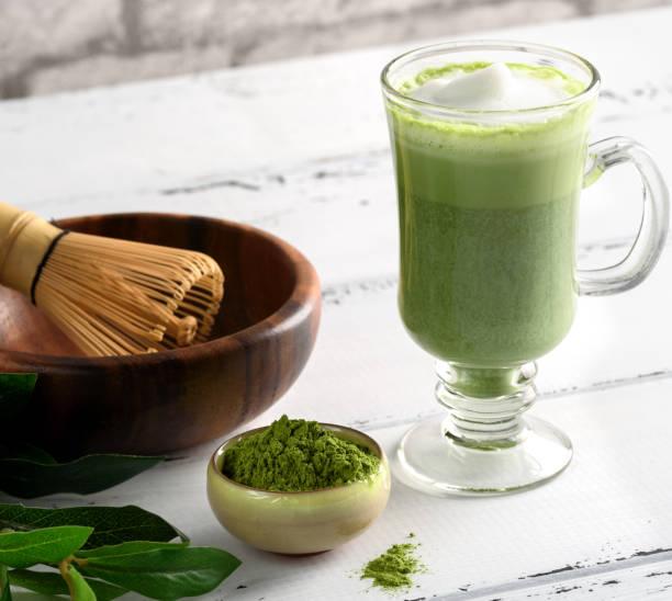 matcha grüner tee latte trinken in glasschale auf weißem hintergrund - grüner tee koffein stock-fotos und bilder