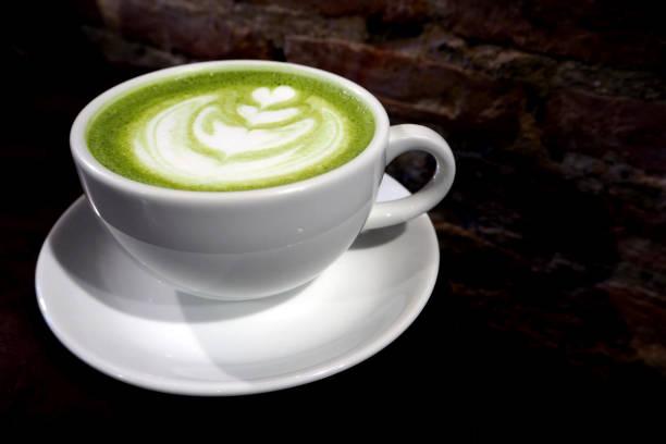 matcha grüner tee latte cup auf ziegel wand hintergrund - grüner tee koffein stock-fotos und bilder