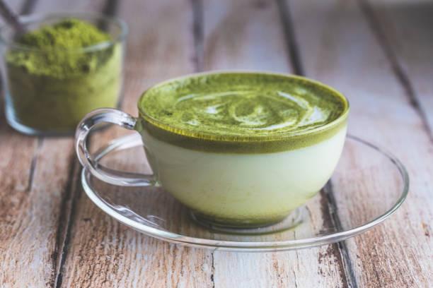 matcha-grünen tee-latte auf einem holztisch. - grüner tee koffein stock-fotos und bilder