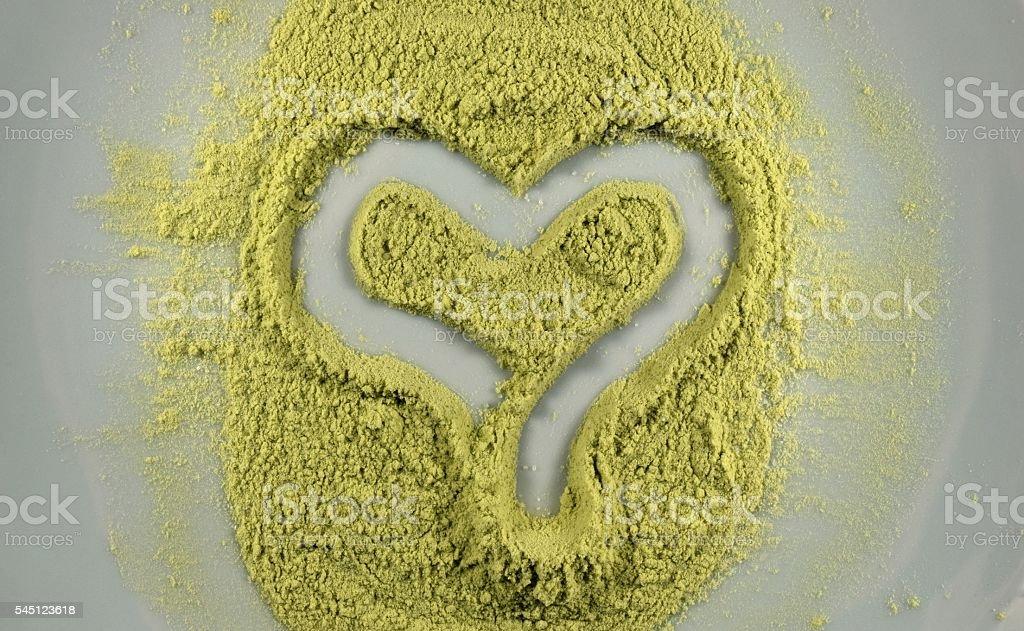matcha green tea powder shaped into a heart stock photo