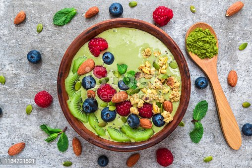 istock matcha green tea smoothie bowl with fresh fruits, berries, nuts, seeds and granola with a spoon for healthy breakfast 1134721521