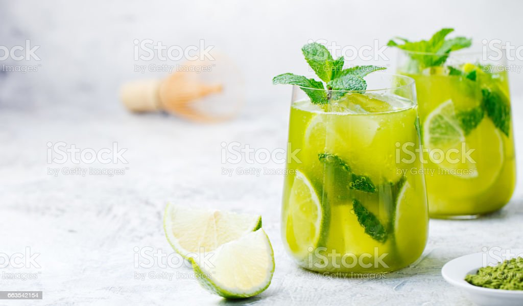 Matcha iced green tea with lime and fresh mint on a marble background. Copy space stock photo