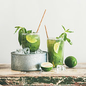 Summer refreshing beverage matcha ice tea with mint and lime in glasses over rustic kitchen cupboard, copy space