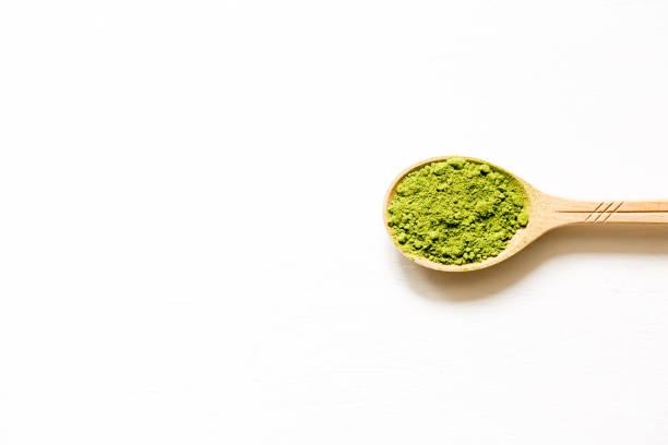 抹茶。白い背景にスプーンで日本の粉末緑茶。 - 抹茶 ストックフォトと画像