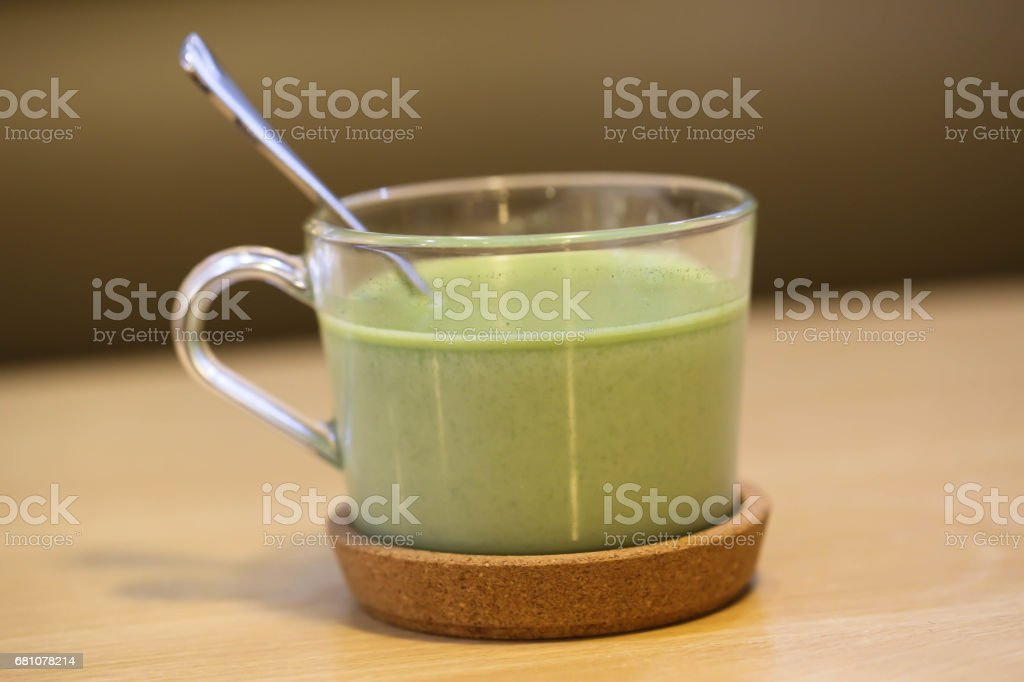 Matcha latte with spoon on the wood table royalty-free stock photo